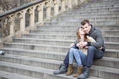 Integral de la mujer cariñosa que besa al hombre mientras que se sienta en pasos al aire libre Imágenes de archivo libres de regalías