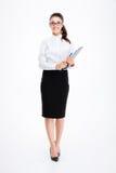 Integral de la mujer de negocios alegre que coloca y que sostiene el tablero imagenes de archivo