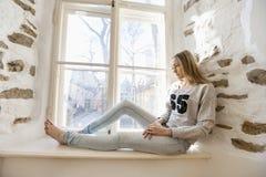 Integral de la mujer joven pensativa que se sienta en travesaño de la ventana en casa Imágenes de archivo libres de regalías