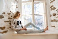 Integral de la mujer joven pensativa que se sienta en travesaño de la ventana en casa Foto de archivo