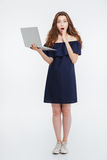 Integral de la mujer joven sorprendente que coloca y que sostiene el ordenador portátil Foto de archivo