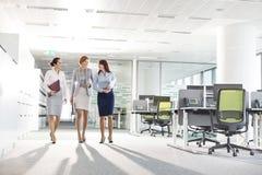 Integral de las empresarias con las carpetas de archivos que caminan en oficina imagenes de archivo