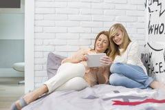 Integral de madre con la hija que usa la tableta en dormitorio Foto de archivo libre de regalías