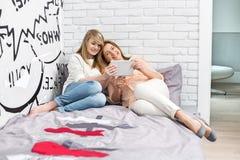 Integral de madre con la hija que usa la tableta en dormitorio Imagenes de archivo