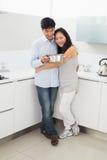 Integral de un hombre de abarcamiento de la mujer en cocina Foto de archivo libre de regalías