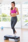 Integral de una mujer del ajuste que realiza ejercicio de los aeróbicos del paso Imagen de archivo