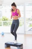 Integral de una mujer del ajuste que realiza ejercicio de los aeróbicos del paso Imagenes de archivo