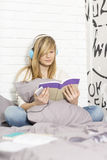 Integral del adolescente que escucha la música mientras que libro de lectura en dormitorio Fotografía de archivo libre de regalías
