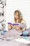 Integral del adolescente que escucha la música mientras que libro de lectura en dormitorio Imagenes de archivo