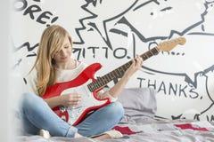 Integral del adolescente que toca la guitarra en dormitorio Imagenes de archivo