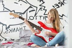 Integral del adolescente que toca la guitarra en dormitorio Imagen de archivo libre de regalías