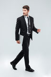 Integral del hombre de negocios joven atractivo que camina y que sostiene el ordenador portátil Imagen de archivo