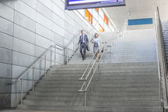 Integral del hombre de negocios y de la empresaria del paseo de las escaleras abajo en el ferrocarril Fotografía de archivo libre de regalías
