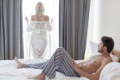 Integral del hombre joven descamisado que mira la ventana del hotel de la mujer que hace una pausa Fotos de archivo