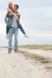 Integral del hombre joven que lleva a cuestas a la mujer en rastro en el campo Imágenes de archivo libres de regalías