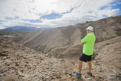 Integral del hombre mayor que mira la visión mientras que se coloca en roca Imagen de archivo
