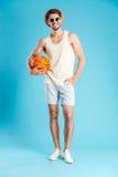 Integral del hombre sonriente que coloca y que sostiene la bola del baloncesto Fotos de archivo