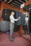 Integral del sastre que hace una pausa el estante de la ropa de trajes fotografía de archivo libre de regalías
