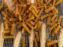 Integral pasta. Spilled with wheat and pasta around Royalty Free Stock Photo
