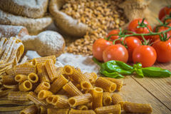 Integral pasta with ingredients ingredients and tomatoes. Royalty Free Stock Photography