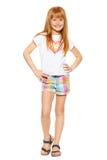Integral una niña alegre con el pelo rojo en pantalones cortos y una camiseta; aislado en el fondo blanco Imagen de archivo libre de regalías