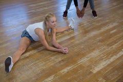 Integrale del ballerino femminile con l'amico che allunga le gambe Fotografie Stock