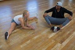 Integrale del ballerino femminile con l'amico che allunga le gambe sul pavimento Immagini Stock