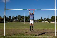 Integrale del giocatore di rugby che appende sul palo al campo Fotografia Stock