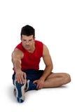 Integrale del giocatore di sport che allunga le gambe mentre esercitandosi Fotografie Stock