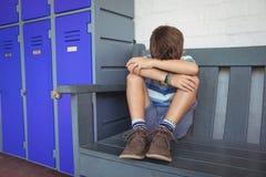 Integrale del ragazzo che si siede sul banco dagli armadi Fotografia Stock