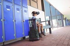 Integrale del ragazzo che usando i vetri di realtà virtuale mentre sedendosi sul banco Fotografia Stock