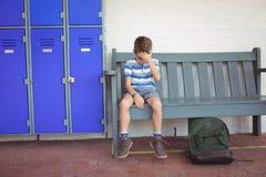 Integrale del ragazzo triste che si siede sul banco dagli armadi Immagine Stock
