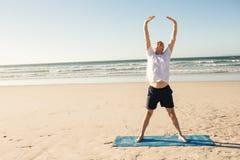Integrale dell'uomo senior che allunga alla spiaggia Fotografia Stock
