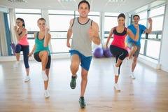 Integrale della classe e dell'istruttore di forma fisica che fanno i pilates eserciti Immagini Stock