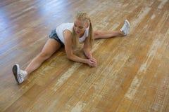 Integrale della donna che allunga le gambe sul pavimento Fotografia Stock Libera da Diritti