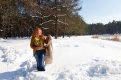 Integrale della donna graziosa allegra che guarda lateralmente e che tiene il suo cappotto a disposizione con gli alberi nevosi s immagini stock libere da diritti