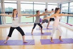 Integrale della gente sportiva che allunga le mani alla classe di yoga Immagine Stock Libera da Diritti