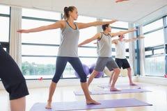 Integrale della gente sportiva che allunga le mani alla classe di yoga Fotografie Stock