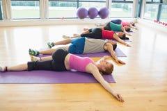 Integrale della gente sportiva che allunga sulle stuoie alla classe di yoga Fotografia Stock