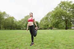 Integrale della giovane donna di misura che esegue allungando esercizio nel parco Immagini Stock Libere da Diritti