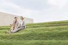 Integrale delle donne di affari con la tazza ed il computer portatile di caffè eliminabile che si siedono sull'erba fa un passo co Fotografia Stock