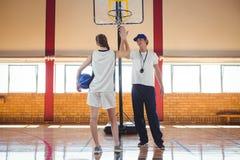 Integrale di alto fiving del giocatore di pallacanestro con l'allenatore maschio Immagine Stock
