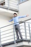 Integrale di giovane condizione sorridente dell'uomo d'affari arma steso al balcone dell'hotel Fotografie Stock