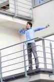Integrale di giovane uomo d'affari che allunga al balcone dell'hotel Fotografie Stock
