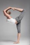 Integrale di una giovane donna che allunga corpo Fondo grigio Fotografie Stock Libere da Diritti