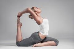 Integrale di una giovane donna che allunga corpo Fondo grigio Fotografia Stock