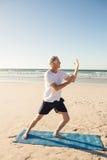 Integrale di yoga di pratica attiva dell'uomo senior alla spiaggia Fotografia Stock Libera da Diritti