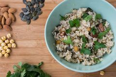 Integraler Reis in einer Schüssel gekocht mit Mandel, Kürbiskerne, Kichererbse und mit Petersilie auf hölzernem Hintergrund be lizenzfreie stockfotos