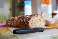 Integrales Brot auf Schneidebrett mit Messer Stockfoto