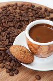 Integrated chocolate cookie and a cup of coffee with raw coffee Stock Images